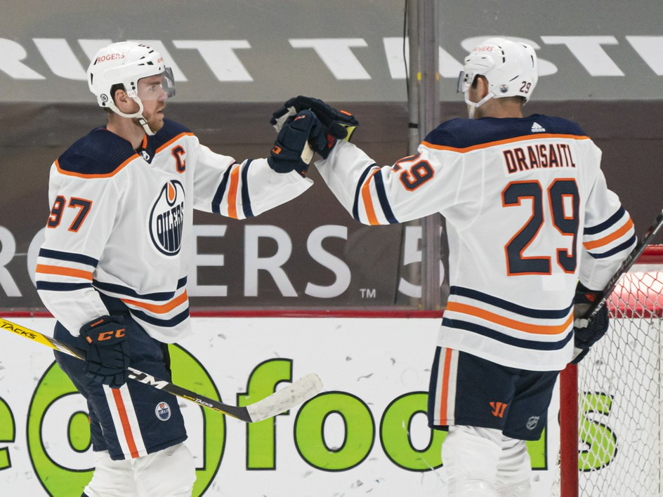 Connor McDavid (97) of the Edmonton Oilers celebrates with teammate Leon Draisaitl (29) after scoring a goal against the Vancouver Canucks at Rogers Arena on May 3, 2021. PHOTO BY RICH LAM /Getty Images
