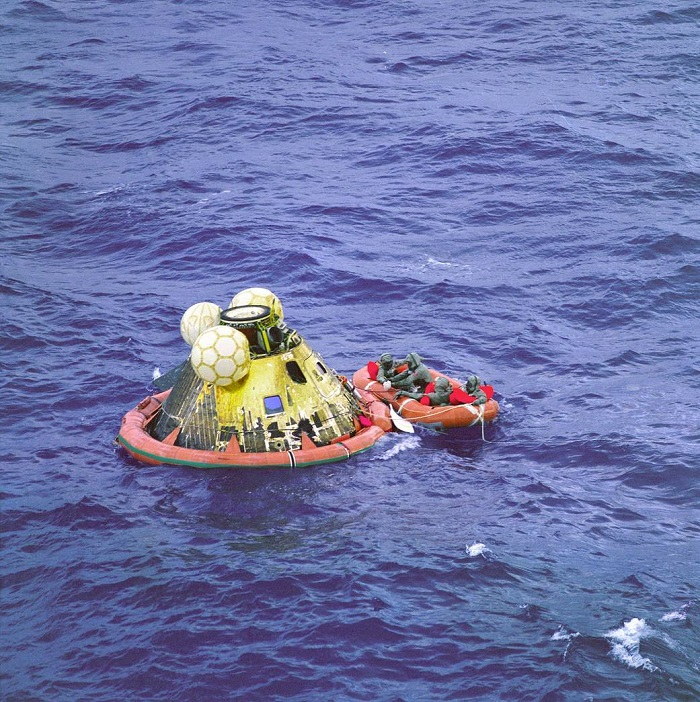 The Apollo 11 crew await pickup by a helicopter from the USS Hornet, prime recovery ship for the historic lunar landing mission. The fourth man in the life raft is a United States Navy underwater demolition team swimmer. All four men are wearing biological isolation garments.